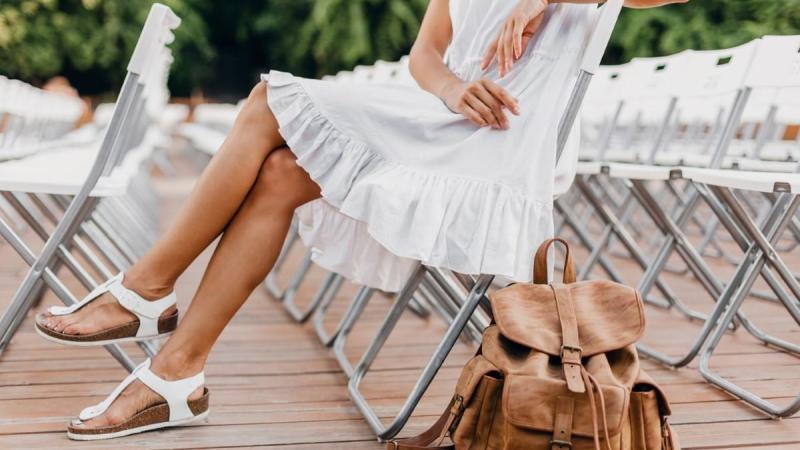 Žena v bílých šatech sedí na sklápěcí židli, jsou jí vidět holé nohy obuté v bílých sandálech a vedle sebe má volně položený kožený batoh.